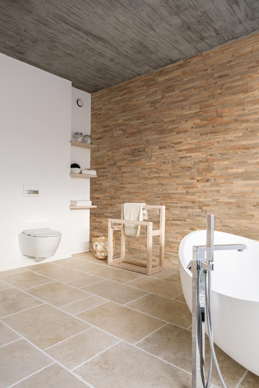 Reclaimed wood wall panels in bedroom with standalone bathtub