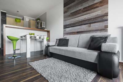 Reclaimed wood boards in apartment interior behind sofa