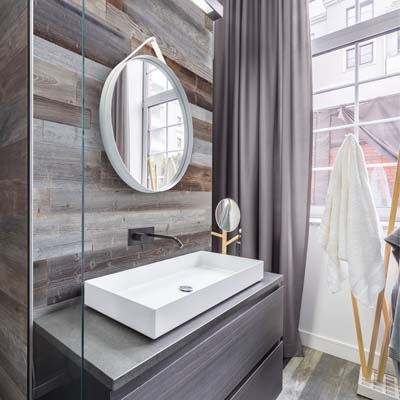 Bathroom interior with grey wood boards behind morror and sink